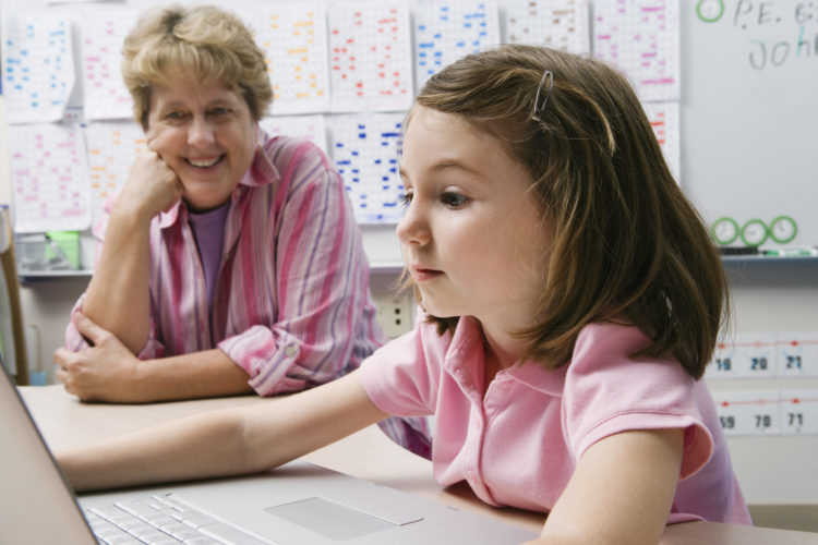 Girl and her teacher looking at a computer screen